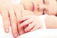 Dé el bebé durmiente en la mano de la madre Foto de archivo