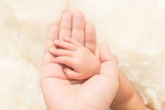 Dé el bebé durmiente en la mano del primer de la madre (focu suave Imagenes de archivo
