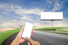 dé el control y la pantalla táctil teléfono elegante con la cartelera en blanco para Fotos de archivo libres de regalías