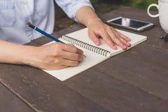 Dé el cuaderno de la escritura de la mujer en la tabla de madera con café de la taza y el pH fotografía de archivo libre de regalías