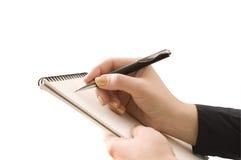 Dé el cuaderno del mantiene y la otra pluma y wri del mantiene de la mano foto de archivo libre de regalías