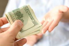 Dé el dinero alguien como soborno para sugerir un sistema corrupto imagen de archivo libre de regalías
