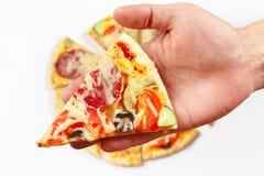 Dé el hombre con un pedazo de primer condimentado de la pizza Fotos de archivo
