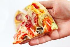 Dé el hombre con un pedazo de primer sabroso de la pizza Foto de archivo