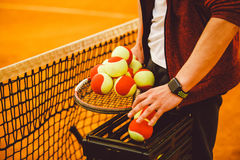 Dé el hombre que lleva a cabo una estafa de tenis y muchas metas Cesta para las pelotas de tenis, imagen de archivo