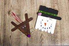 Dé el muñeco de nieve hecho a mano y el reno del polo que ponen en un fondo de madera del grano Imágenes de archivo libres de regalías