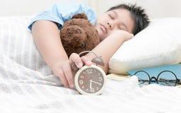 Dé el muchacho que alcanza para apagar el despertador en la cama Imagen de archivo