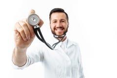 Dé el primer, sosteniendo un estetoscopio, retrato de un doctor joven imagen de archivo