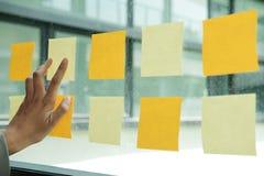 dé el tacto en notas adhesivas sobre la pared de cristal Papel de nota pegajoso con referencia a imagenes de archivo