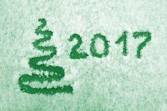 Dé escrito 2017 y resuma el árbol de Navidad en nieve Año Nuevo y tarjeta de Navidad en verde Foto de archivo libre de regalías