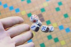 Dé a fondo blanco de los dados que lanza el juego de mesa borroso colorido El momento dinámico del juego, foco selectivo Fotografía de archivo libre de regalías