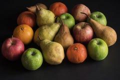 Dé fruto en el fondo negro, manzana, pera, naranja, mandarín Fotos de archivo