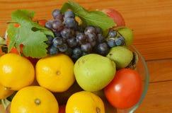Dé fruto en un bol de vidrio en una tabla de madera Imagen de archivo