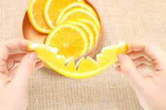 Dé fruto en un cuenco de madera en su naranja rasgada mano, lista para el consum Fotos de archivo