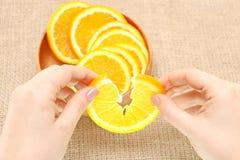 Dé fruto en un cuenco de madera en su naranja rasgada mano, lista para el consum Foto de archivo