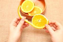 Dé fruto en un cuenco de madera en su naranja rasgada mano, lista para el consum Imágenes de archivo libres de regalías