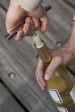 Dé la apertura de una botella de vino con un sacacorchos Imagen de archivo libre de regalías
