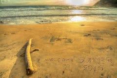 Dé la bienvenida al verano 2015 que escribe en la puesta del sol Imagen de archivo libre de regalías