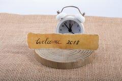 Dé la bienvenida a 2018 escrito el papel y el reloj rasgados del alalrm Imágenes de archivo libres de regalías