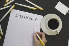 Dé la escritura de resoluciones del ` s del Año Nuevo, de plumas blancas y de una insignia Fotos de archivo