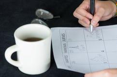 Dé la escritura en el calendario de papel al lado de la taza de café Imagen de archivo