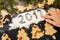 Dé la escritura 2017 en la harina con el dulce del pan de jengibre Fotos de archivo