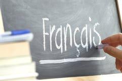Dé la escritura en una pizarra en una clase de lengua con la palabra y el x22; French& x22; escrito en él Imágenes de archivo libres de regalías