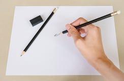 Dé la escritura por el borrador de lápiz en el Libro Blanco y borre el caucho en el escritorio fotografía de archivo