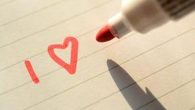 Dé la escritura TE AMO de U con el marcador rojo en el papel alineado almacen de video