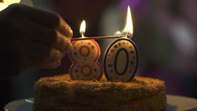 Dé la iluminación de la torta de cumpleaños de las velas, celebración de 80 aniversarios, postre sabroso almacen de video
