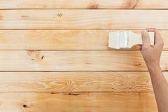 Dé la laca del claro del cepillo de pintura en la superficie de madera Fotos de archivo