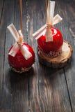 Dé la manzana de caramelo sumergida cubierta con multicolor asperja Fotografía de archivo libre de regalías