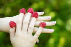 Dé la muchacha con las frambuesas en los fingeres y manicura francesa imagen de archivo libre de regalías