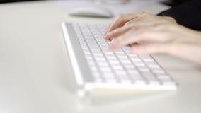 Dé la mujer de negocios que mecanografía en el teclado de ordenador en la oficina almacen de metraje de vídeo