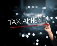 Dé la pluma de tenencia y escriba la amnistía de impuesto redacta, chispea el backg ligero Imagen de archivo