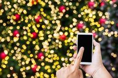 Dé la prensa en la pantalla grande del smartphone en golde del tema del Año Nuevo de Navidad Foto de archivo