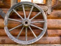 Dé la rueda de hilado en la pared de la cabaña de madera vieja en el pueblo ruso Imagen de archivo libre de regalías
