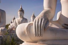 Dé la situación blanca de Buda en fondo del cielo azul Foto de archivo libre de regalías