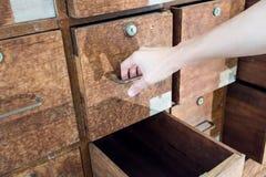 Dé la tracción de un cajón del gabinete de madera frecuentado viejo Fotografía de archivo