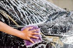 Dé lavar un coche con un paño de la microfibra Imagen de archivo