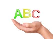 Dé llevar a cabo el símbolo de ABC de las letras en el fondo blanco Fotos de archivo