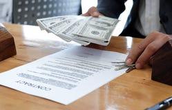 Dé llevar a cabo llave y dólares de la casa con el documento del acuerdo y m fotos de archivo