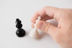 Dé llevar a cabo un pedazo de ajedrez en el fondo blanco Fotos de archivo libres de regalías