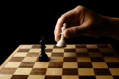 Dé llevar a cabo un pedazo de ajedrez en fondo negro Foto de archivo