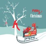 Dé los árboles exhaustos del invierno con las bufandas de la Navidad con el trineo con los regalos de Navidad, Foto de archivo