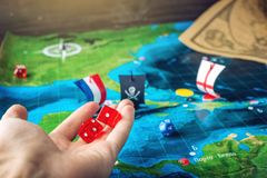 Dé los dados rojos que lanzan en el mapa del mundo de los juegos de mesa hechos a mano del terreno de juego con un barco pirata Fotos de archivo libres de regalías