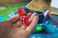 Dé los dados rojos que lanzan en el mapa del mundo de los juegos de mesa hechos a mano del terreno de juego con un barco pirata Imagen de archivo