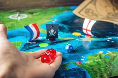 Dé los dados rojos que lanzan en el mapa del mundo de los juegos de mesa hechos a mano del terreno de juego con un barco pirata Imagen de archivo libre de regalías