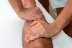 Dé masajes al terapeuta Massaging una pierna del ` s del hombre Imagenes de archivo