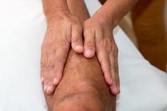 Dé masajes al terapeuta Massaging una pierna del ` s del hombre Imagen de archivo